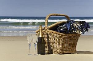 cesta pronta para um piquenique na praia com duas taças de champanhe foto