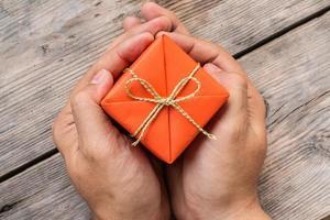 mão segurando uma caixa de presente laranja e fita amarela