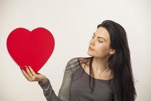 menina segurando coração com doce foto
