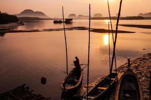 silhueta de pescador e barcos tradicionais tailandeses em Sam Chong