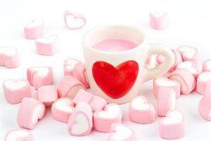 símbolo de coração vermelho no copo de leite e coração de doce rosa foto