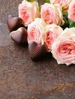 corações doces de chocolate e rosas cor de rosa foto