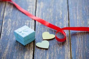 dois corações moldam brinquedos e presentes em fundo de madeira.