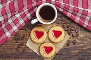 xícara de café e biscoitos com geléia de morango foto