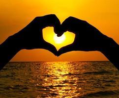 silhueta mão em forma de coração e nascer do sol sobre o oceano