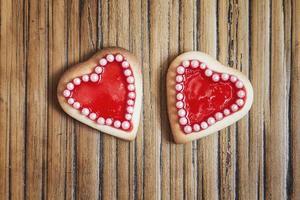 dois cookies de corações vermelhos em fundo de madeira foto
