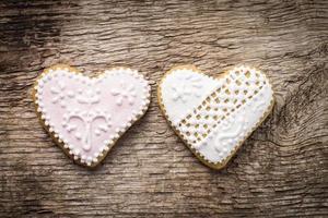 dois cookies decorativos de coração em fundo de madeira texturizada foto