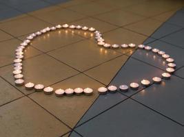 formato de coração de velas acesas no chão