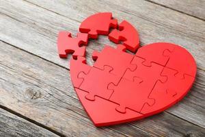 coração quebra-cabeça vermelho sobre fundo cinza de madeira foto