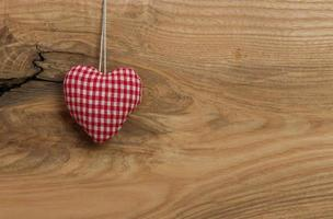 amo coração pendurado em fundo de textura de madeira foto