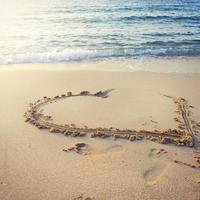 coração escrito na areia. foto