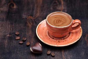xícara de café expresso e chocolates foto