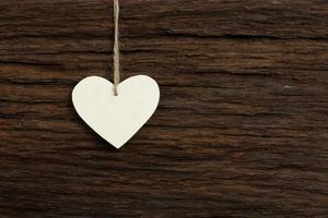 branco amor dia dos namorados coração pendurado fundo de textura de madeira foto