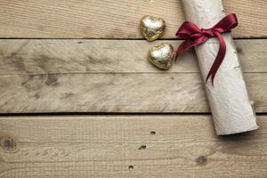 papel de carta e corações de ouro em fundo de madeira