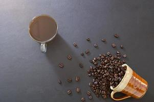canecas de café e grãos de café na mesa foto