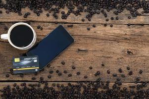 smartphone e um cartão de crédito, uma caneca de café e grãos de café na mesa foto