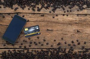 smartphone, cartão de crédito e grãos de café na mesa foto