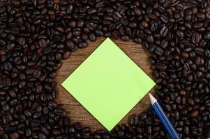 papel, lápis e grãos de café na mesa