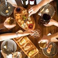 pessoas bebendo vinho e comendo lanches