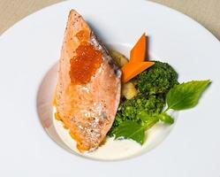refeição de salmão com caviar e vegetais foto