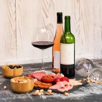 garrafa de vinho, copo com salsichas salgadas