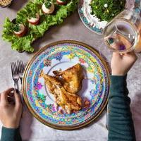 mulher segurando vinho branco enquanto está sentada à mesa