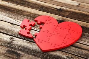 coração de quebra-cabeça vermelho em fundo de madeira marrom