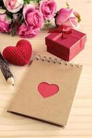 bloco de notas em branco com caixa de presente vermelha e formato de coração vermelho foto
