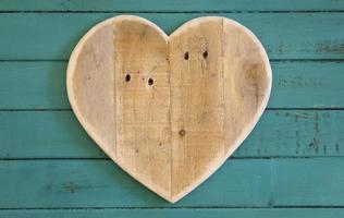 amo dia dos namorados coração de madeira em fundo pintado de turquesa foto