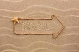 corda de flecha com a palavra brasil na areia foto