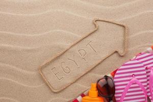 ponteiro egípcio e acessórios de praia na areia foto