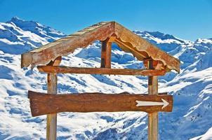 placa de madeira rústica em branco, fundo de montanha com neve foto