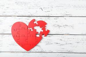 coração quebra-cabeça vermelho sobre fundo branco de madeira