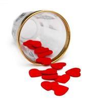 pequenos corações de madeira derramando do vidro no branco foto