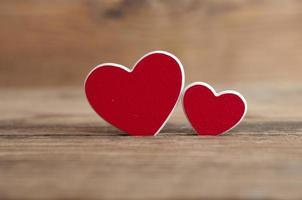 dois corações vermelhos em fundo de madeira foto