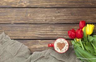 cappuccino com formato de coração e buquê de tulipas foto