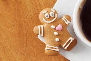 Homem-biscoito sorridente e xícara de café foto