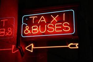 sinal de néon, táxi e ônibus foto