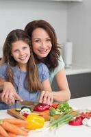 mulher com filha cortando legumes na cozinha foto