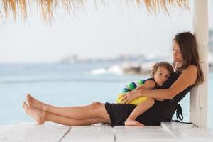 linda jovem mãe, abraçando seu filho na praia