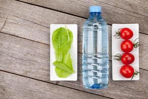 folhas de salada verde, garrafa de água e tomates foto