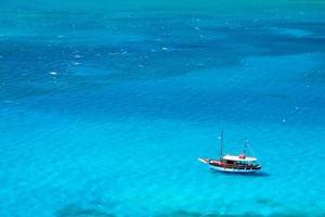 barco grego flutua em águas turquesa brilhante foto