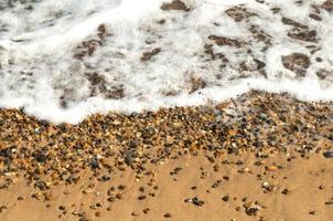 ondas do mar batem na areia e na praia de seixos