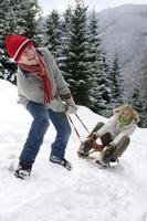 homem puxando namorada em um trenó em uma colina remota com neve