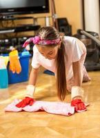 menina lavando chão de madeira com pano na sala de estar foto