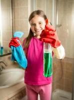 garota sorridente posando com pano e spray de limpeza no banheiro