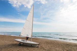 pequeno veleiro em um carrinho na praia foto