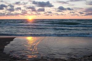 pôr do sol refletido em ondas quebradas na praia