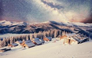 chalés nas montanhas à noite sob as estrelas foto