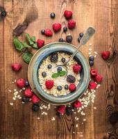mingau com leite, frutas vermelhas em uma tigela de rustik no fundo de madeira foto